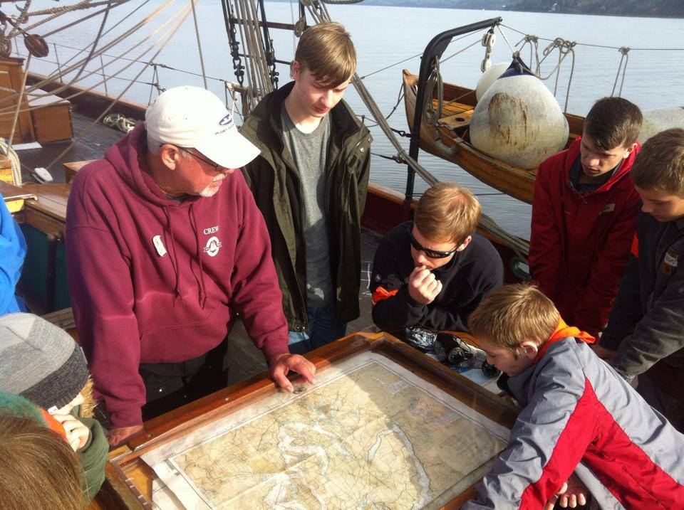 People gathered around a map while on the deck of a boat