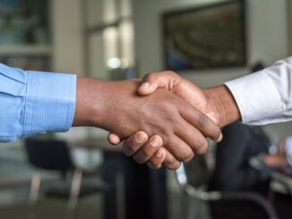 • Two Black people shaking hands. Photo by Cytonn Photography on Unsplash.